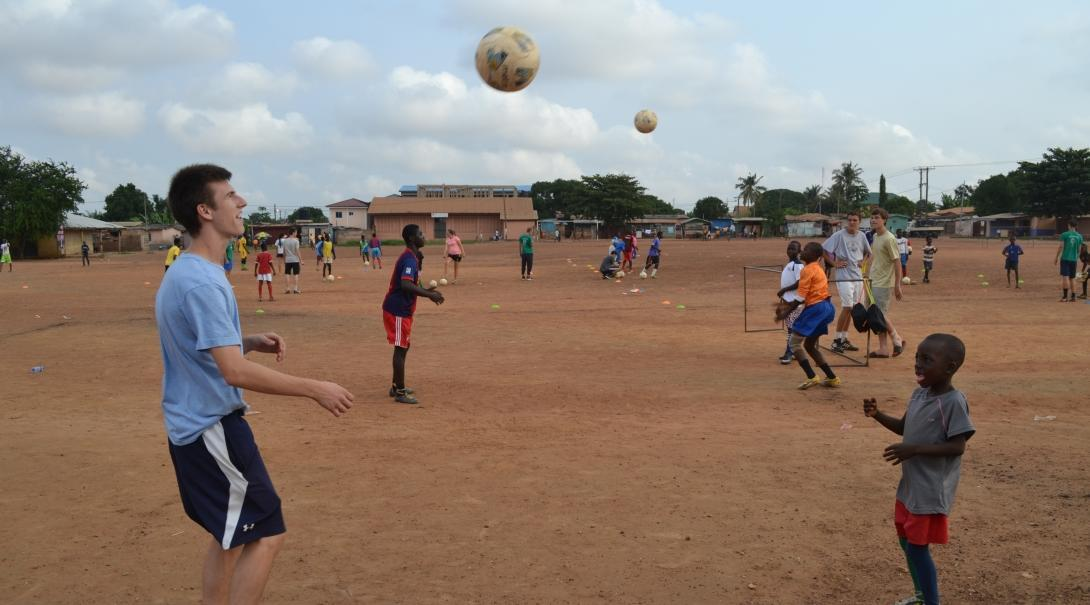 A gap year volunteer practices football drills with a young player at a Football Project in Ghana, Africa.